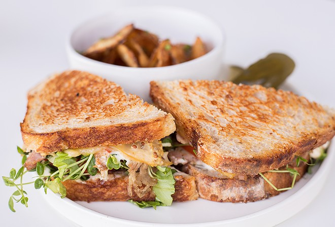A porchetta sandwich is served on rustic bread with garlic-herb aioli-mustard and smoked cheese. - MABEL SUEN