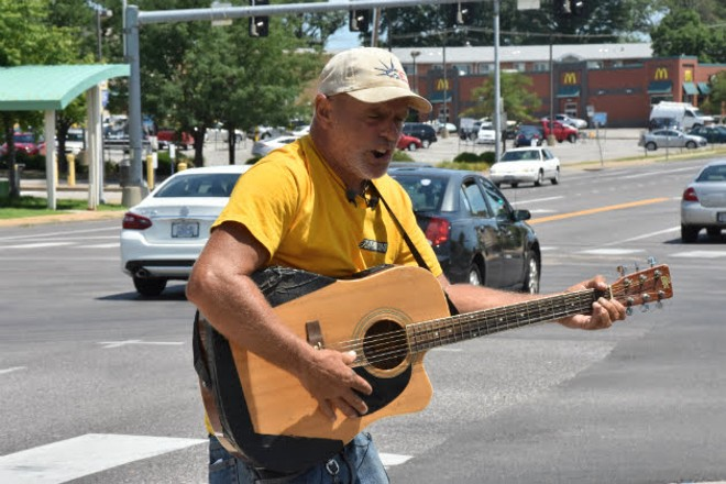 Roger 'Guitar Man' Ulrich playing a backup guitar after his was stolen on Monday. - DOYLE MURPHY