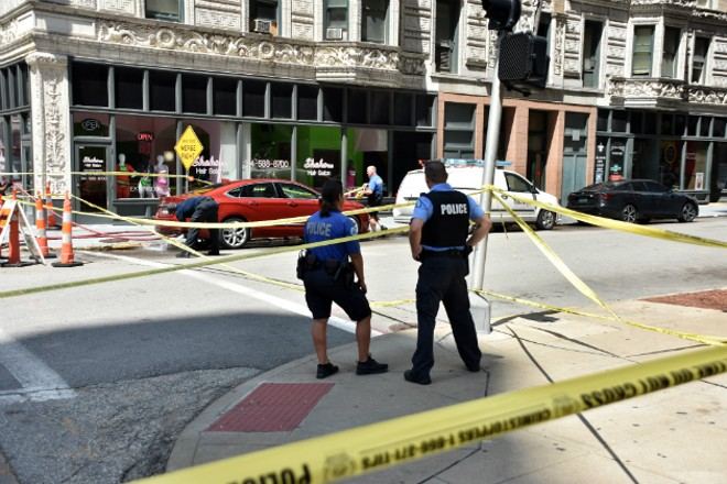 A St. Louis firefighter hoses blood off the street after a deadly shooting downtown. - DOYLE MURPHY