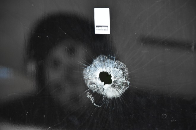 A police sticker marks a bullet hole in the glass of Shah's Hair Salon. - DOYLE MURPHY