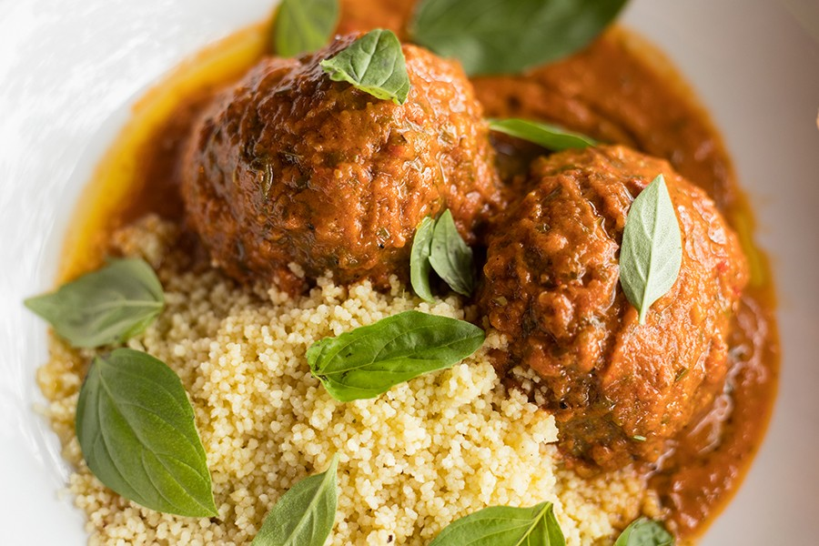 Lamb meatballs are served with smoked tomato sauce, ras el hanout and couscous. - MABEL SUEN