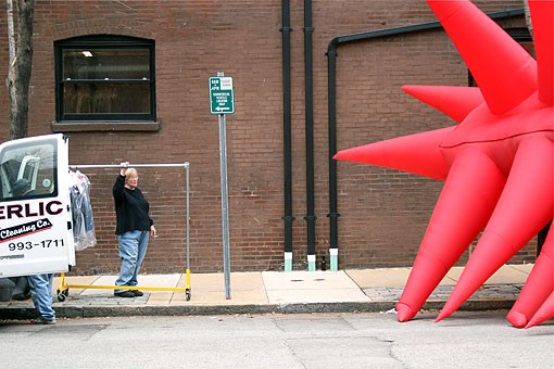 A woman holds onto a clothes rack, gazing at the giant red blob. - PHOTO: NICK SCHNELLE