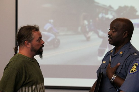Captain Ronald Johnson and motorcyclist Jason Cadell argue about the methods employed by police during Ride of the Century. - DANNY WICENTOWSKI