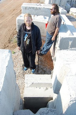 """Robert Stief stands in front of what he calls a """"concrete tomb"""" where he was trapped earlier this month. His friend behind him, Brett Dagoberg, searched for him for hours. - LINDSAY TOLER"""