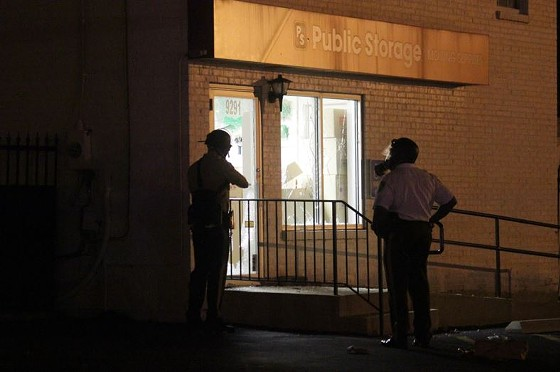 Officers inspect damage at a Ferguson storage company after clearing the streets with tear gas. - DANNY WICENTOWSKI