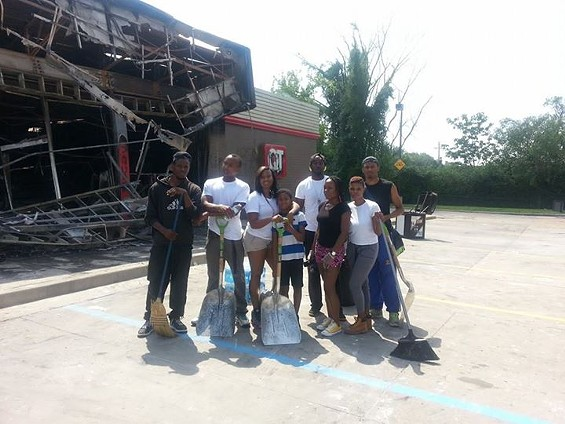 Volunteers clean at the QuikTrip after riots on Sunday night. Erica Hampton is in the middle holding a shovel. - KATHRYN BANKS
