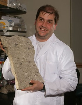 Fike and a 443-million-year-old limestone slab containing the fossilized remains of extinct sea creatures. - IMAGE VIA