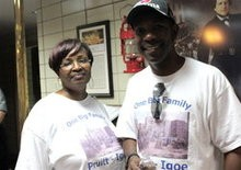 """Sarah and Donnell Phillips in St. Louis Fire Department headquarters, which they knew as the Pruitt-Igoe health clinic where they received vaccinations as kids. Their """"One Big Family Pruitt-Igoe"""" t-shirts come from the annual reunion."""