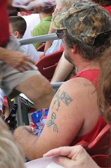 This Cardinals fan shouldn't have any problem entering the ballpark, despite his camo hat and Rebel flag tatoos. - FLICKR.COM/PHOTOS/BK1BENNETT