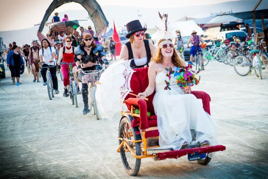 Courtney Lang, from St. Louis, peddles Jessica across the playa to their wedding chapel. - SARAH CROSS
