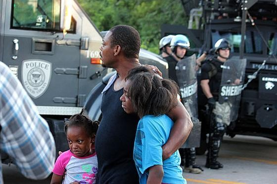 A family watches police in riot gear move into Ferguson in the early days of the August protests. - DANNY WICENTOWSKI