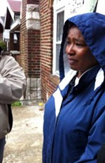 Angelia Williams looks on tearfully as police officers and movers prepare to enter her home. - LEAH GREENBAUM