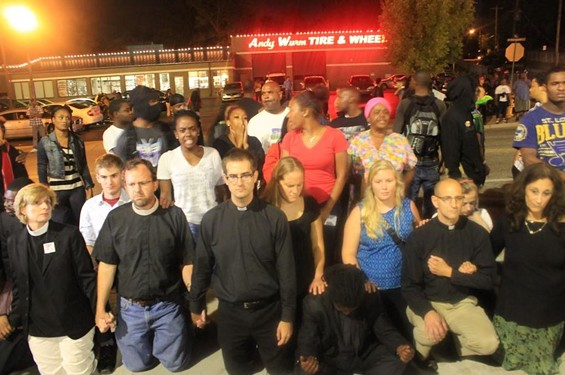 Clergy form a barrier between police and protesters in Ferguson in September. - RAY DOWNS