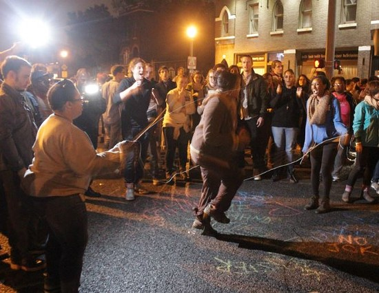 Protesters used hopscotch and other games while blocking an intersection in the Grove Sunday night.