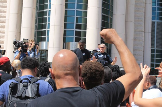 Protesters rally in front of the Thomas Eagleton Courthouse Tuesday. - RAY DOWNS