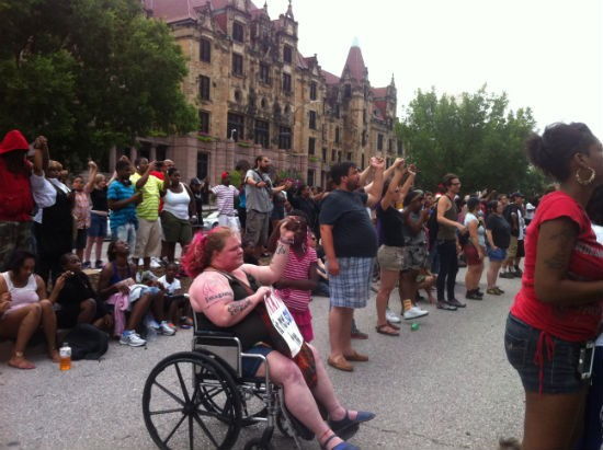 Speaker at the Justice Center asked participants to join hands for a silent prayer. - LEAH GREENBAUM