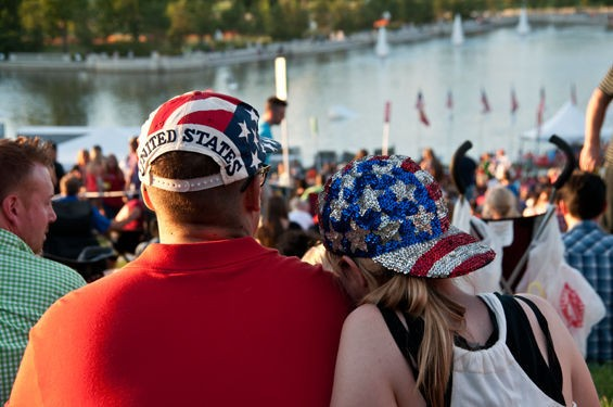 A couple with two impressively American ball caps watches the festivities on Art Hill at Fair St. Louis 2014. - CAROLINE YOO