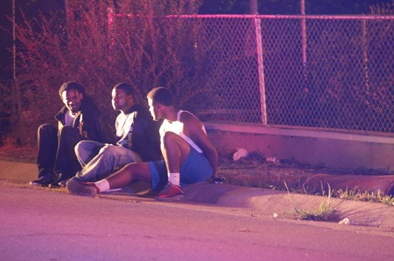 Three men handcuffed on sidewalk on the corner of Florissant and Chambers at 12:15 a.m., just before police shot and injured a man. - DANNY WICENTOWSKI