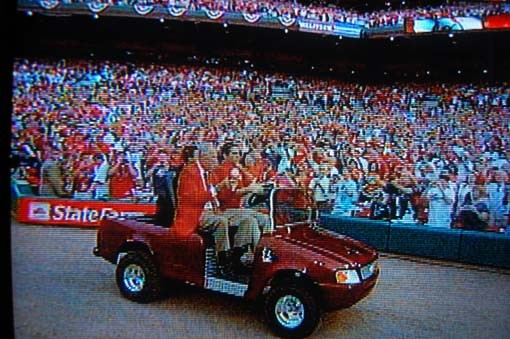 Stan Musial rides out in a customized Mercedes-Benz golf cart and shakes a baseball at the cheering fans.