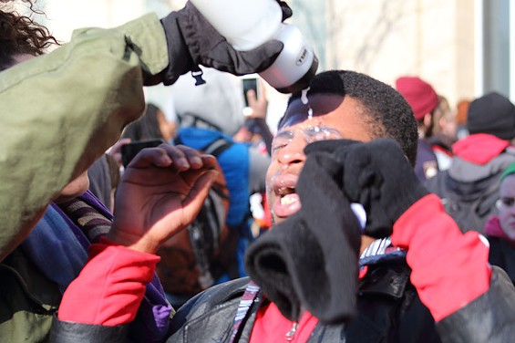 A protester flushes out his eyes after being pepper sprayed by police.