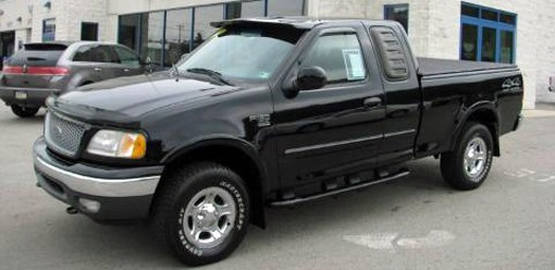A black 1999 Ford F-150 extended cab pickup truck.