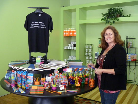 """Nancy Smith shows off her wares. The t-shirt reads, """"All people are born right-handed, but only the GREATEST overcome it."""""""