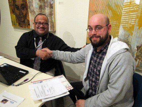 James Lovings, a CAASTL counselor, signs Tim Rakel (R) up for health insurance. - VLAA