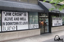 Lure responds yesterday with signs accusing the city of racism. - INSIDESTL.COM