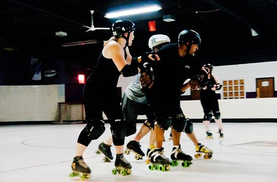 Roller derby players from St. Louis' top male and female teams practice together at the St. Louis Skatium. - CAROLINE YOO