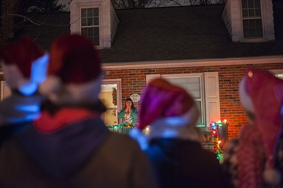 Born and raised in Ferguson, resident Vicki Salsman clasps her hands to her face in joy as Maxine Harris and the other carolers sing.