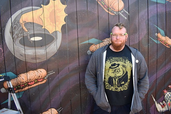 Jason Spencer with an in-process mural he's painting for the Gramophone's patio. - DANIEL HILL