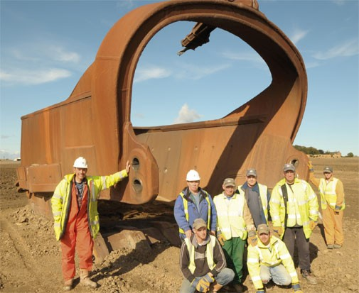 Workers pose before a dragline bucket in the United Kingdom. - WIDDRINGTON.JOURNALLIVE.CO.UK