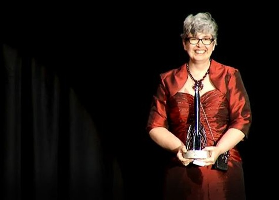 Shrewsbury resident Ann Leckie holds up her Hugo Award for Best Novel at the World Science Fiction Convention in London on August 17. - VIA