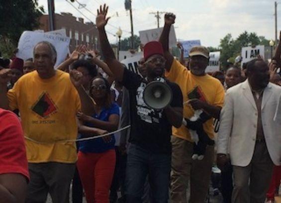 Baruti, left, marches in Ferguson on August 11. - MITCH RYALS