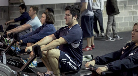 """Before working out, teammates get their blood pumping on the rowing machine."""