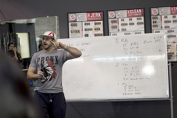 """Mike Walerius, co-owner of Crossfit26 gym, explains the exercises of the day to the team."""