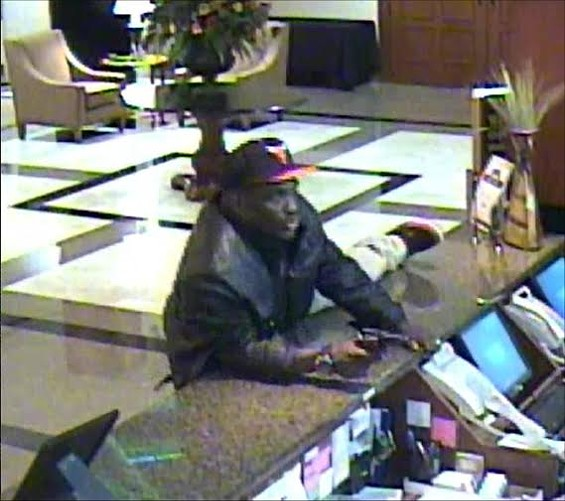 "This still from the Drury Inn & Suites security camera footage shows the suspect who shot and killed a night manager. Police say the man was wearing a Chicago Bulls ball cap, a black or brown leather waist-length coat, a black tee shirt with white ""Adidas"" logo across the front and khaki pants. - SLMPD"