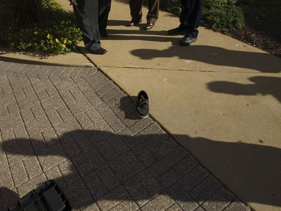 St. Louis detectives gather near one of Yongsang Soh's shoes at the scene of his death.