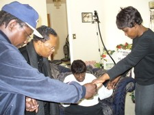 "Family and friends of Charles ""Cookie"" Thornton pray Friday morning. From left to right: Arthur Thornton, Rev. Anthony Stevens, Annie Bell Thornton and Velma Madison. - MAPS.GOOGLE.COM"