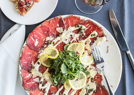 Peppered beef carpaccio, a thinly sliced beef fillet with mustard dressing, arugula, shaved parmesan, capers and lemon.   Jennifer Silverberg