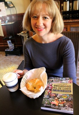 Amanda Doyle with a croissant and cappuccino from Rue Lafayette, a destination in her guidebook. - MABEL SUEN