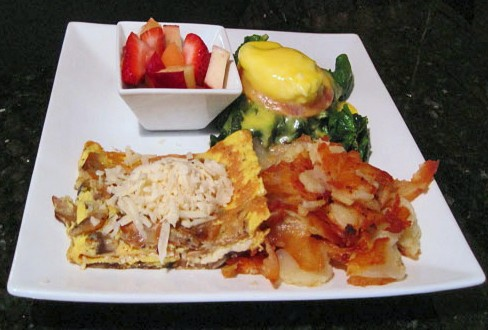 Eggs florentine and kaşar cheese omelet, portions thoughtfully split between two plates. - KRISTIE MCCLANAHAN