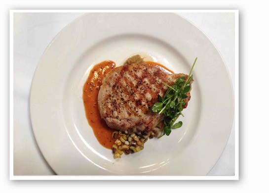 "The ""Rain Crow Ranch Berkshire Bone-in Pork Chop"" with local crowder peas and corn, with a        grain mustard jus. 