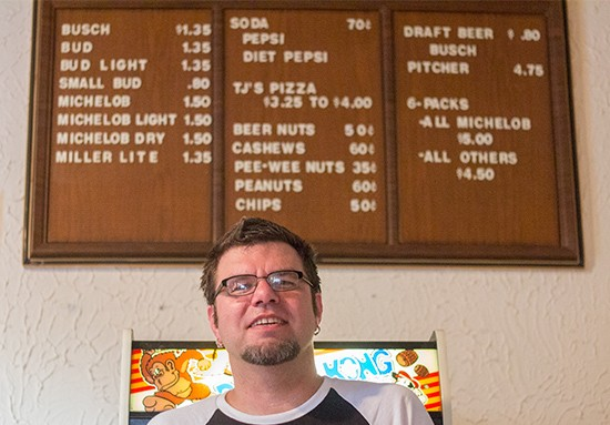 Co-owner Thomas Crone in front of some of Tick Tock Tavern's vintage signage.