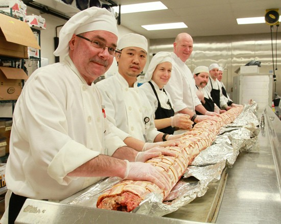 Chef John Johnson (fourth from left) and staff with a 200-pound trial run of a hog log. - IMAGE VIA