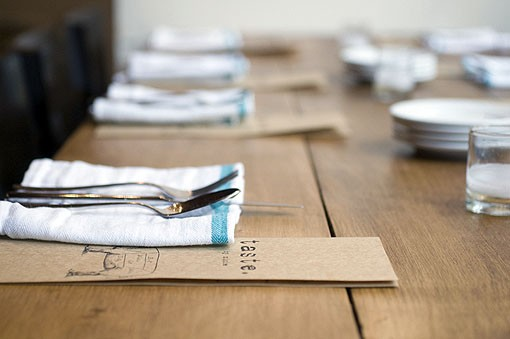 The table settings at Taste are simple and lovely. Linen striped napkins on a rustic wood table. See a slideshow of photos from Taste by Niche. - PHOTO: JENNIFER SILVERBERG