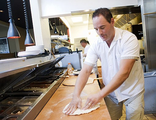 John Racanelli, owner of the Racanelli Empire, says one of the secrets to his pizza is working it on the board. The more you work it, the more air you get out of the dough, creating fewer air bubbles when cooking. View more photos from inside Racanelli's Cucina. - PHOTO: JENNIFER SILVERBERG