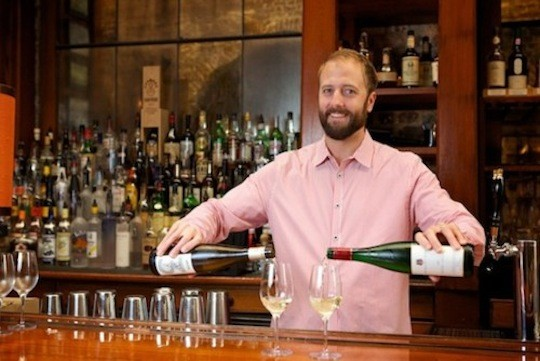Clint Sloan pouring champagne | image via