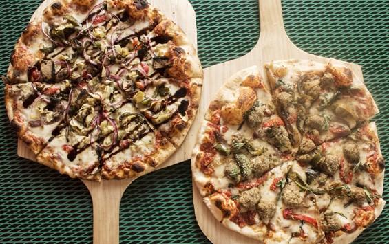 """Veggie"" pizza with tomato sauce, roasted eggplant, peppers, zucchini, onion, mozzarella, provolone and fresh basil; ""Hey Bauly"" pizza with tomato sauce, mini meatballs, peppers, onions, mozzarella, provolone and fresh basil. | Mabel Suen"