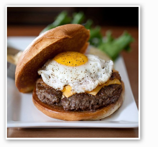 """The """"Breakfast of Champions"""" burger from Five Star, with a sunny-side-up egg, American cheese, roast tomato-bacon jam and hollandaise sauce. 